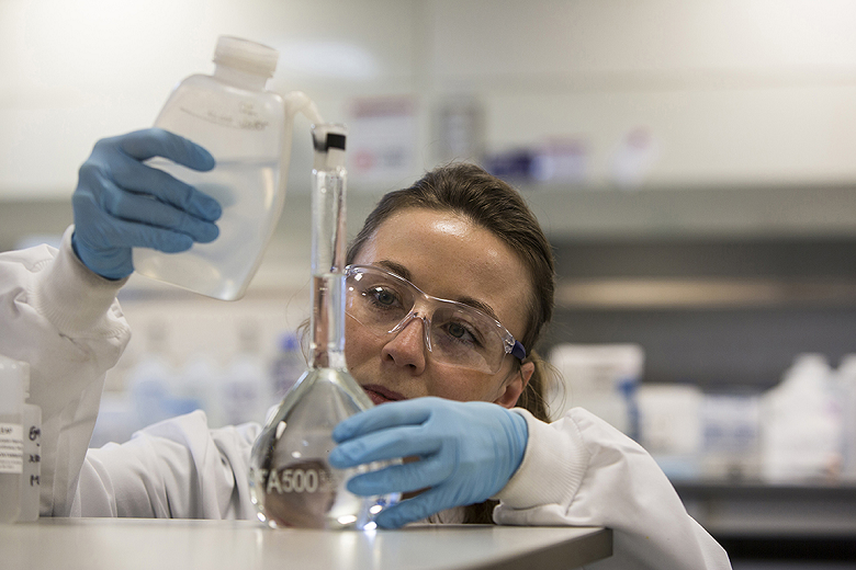 A water analyst filling a volumetric flask