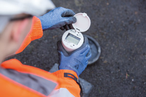 A picture of a small round silver water meter with a digital screen on the top being held by a technician wearing blue gloves, orange jacket and white helmet.