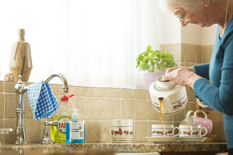 A lady pouring tea by the kitchen sink