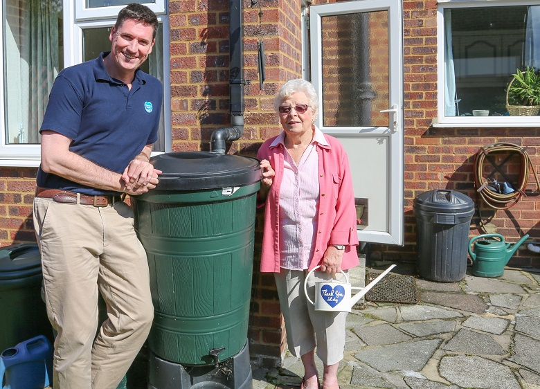Shirley Cato standing next to her water butt with a Thames Water employee