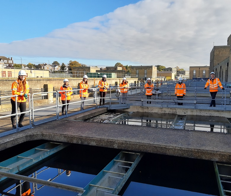 Eight Thames Water graduates dressed in orange PPE stand around a water tank