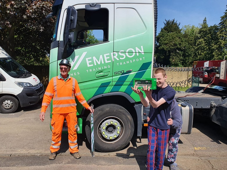Mitchell Sterne being presented with a scale model crane infront of Emerson delivery truck