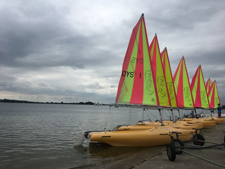 sailing boats on a reservoir under cloudy skies