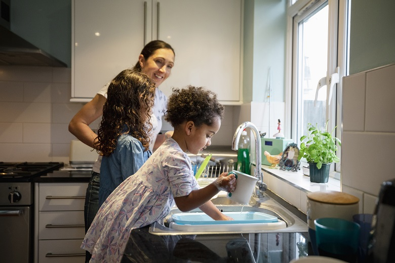 A woman and two children washing up in the kitchen
