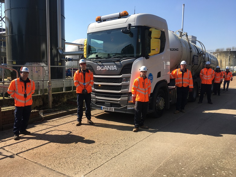 Truck drivers standing around a truck on a Thames Water site