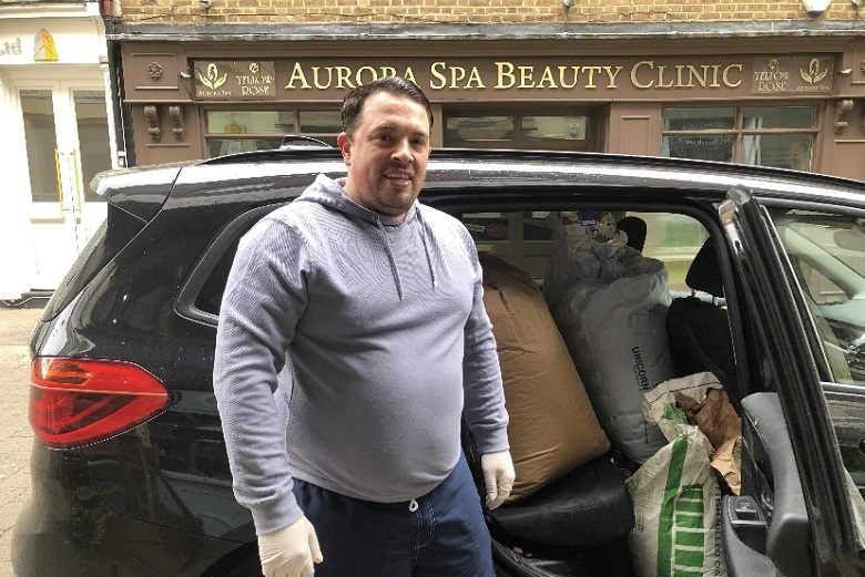 Dean Vine standing with a car full of food for delivery.