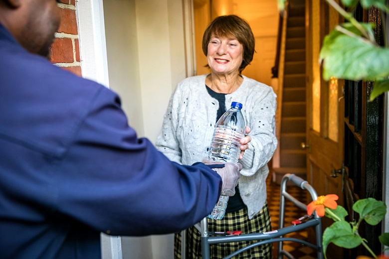 An older lady at her front door receiving a bottled water delivery