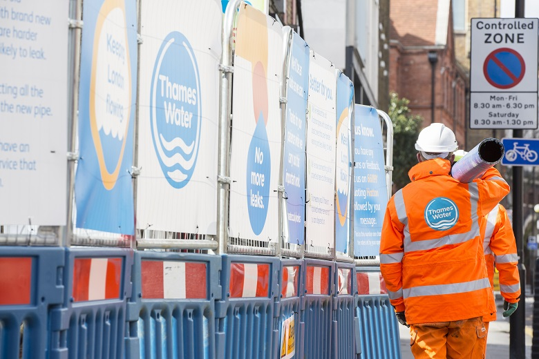 Thames Water engineers carrying a water pipe