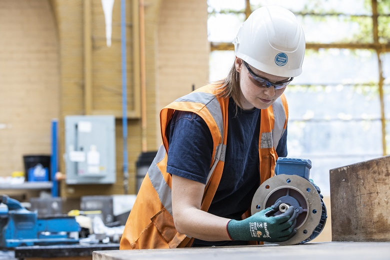 Woman in white hard hat examines motor