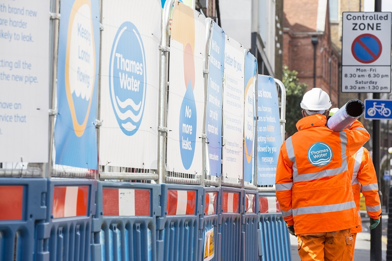 Two engineers wearing orange overalls carry a pipe in front of a Thames Water sign.