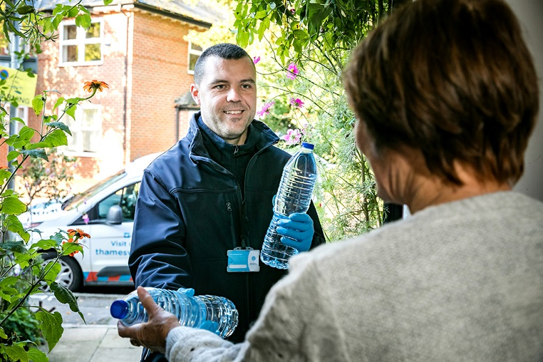 A Thames Water employee dressed in blue hands bottled water to an older lady in grey jumper