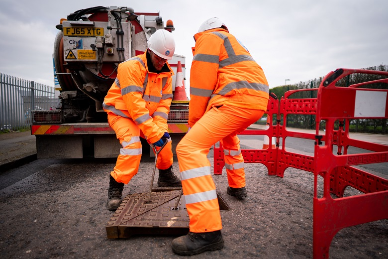 Two technicians in PPE replace a manhole cover