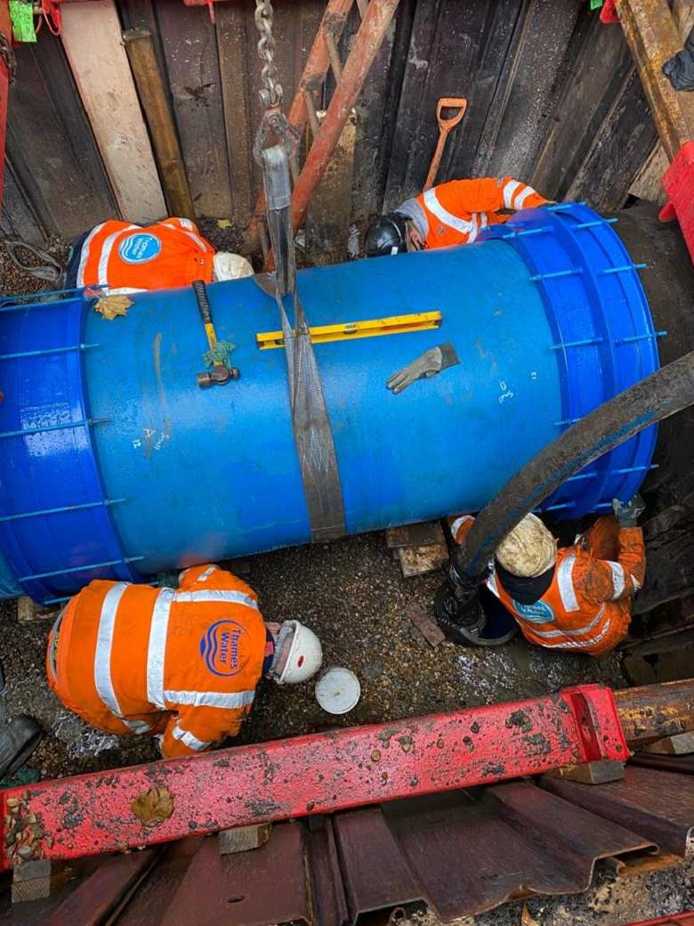 Thames Water engineers fit a section of water main