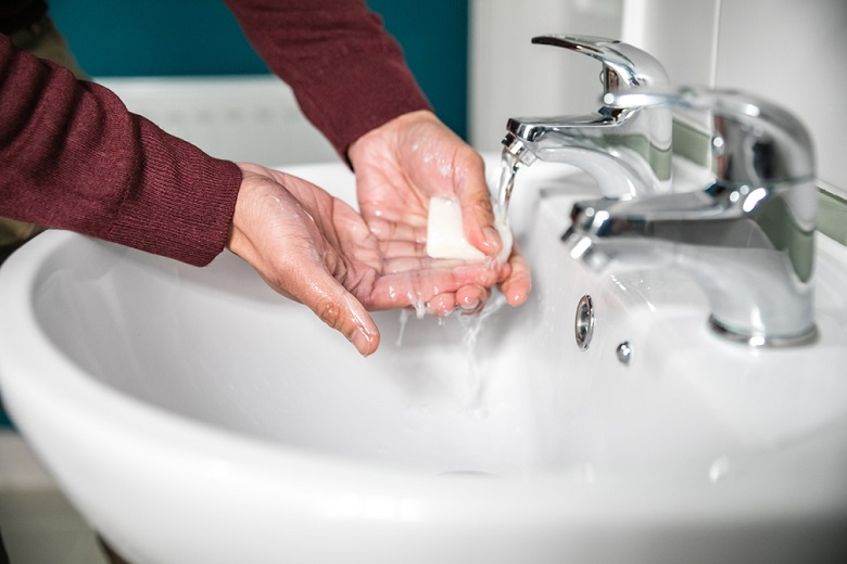 A person in a red jumper washes their hands in a sink