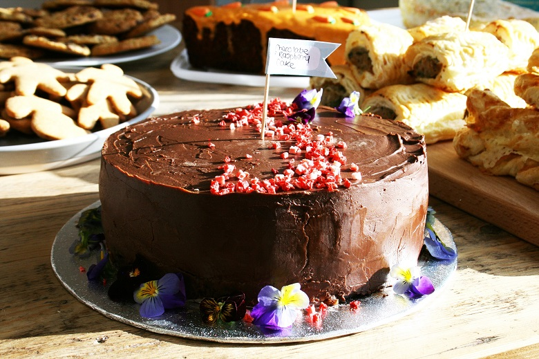A round chocolate cake with purple flowers on it.
