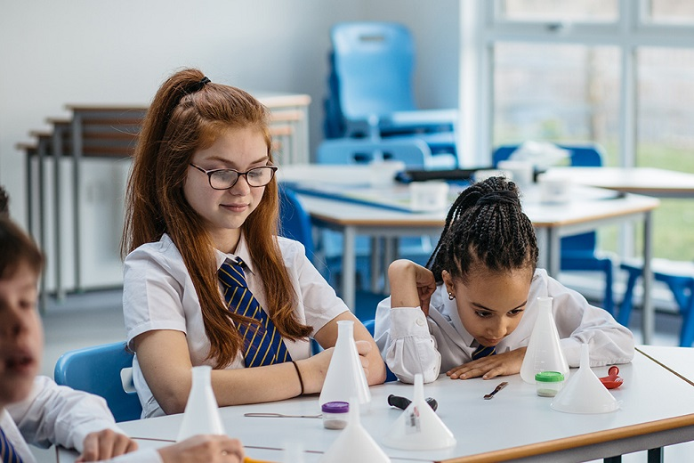 Two school children take part in a water experiment