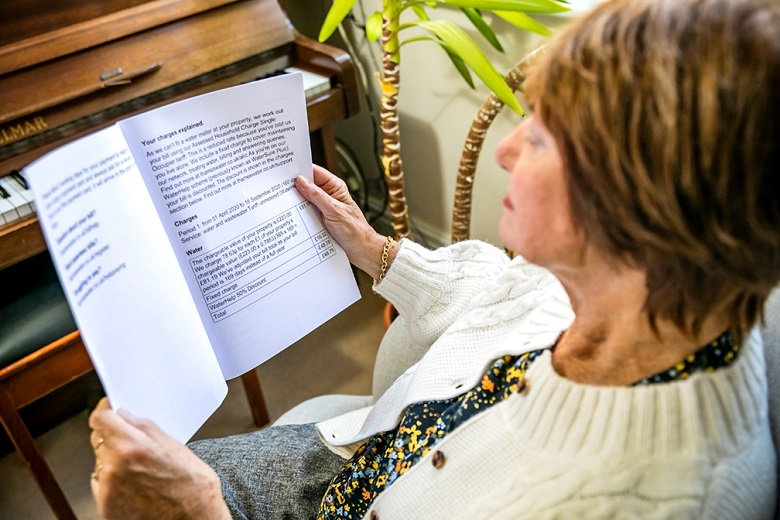 A woman in a white cardigan reads a large print bill