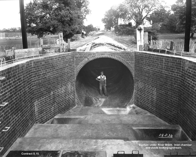 A man stands in a network tunnel at Mogden sewage works