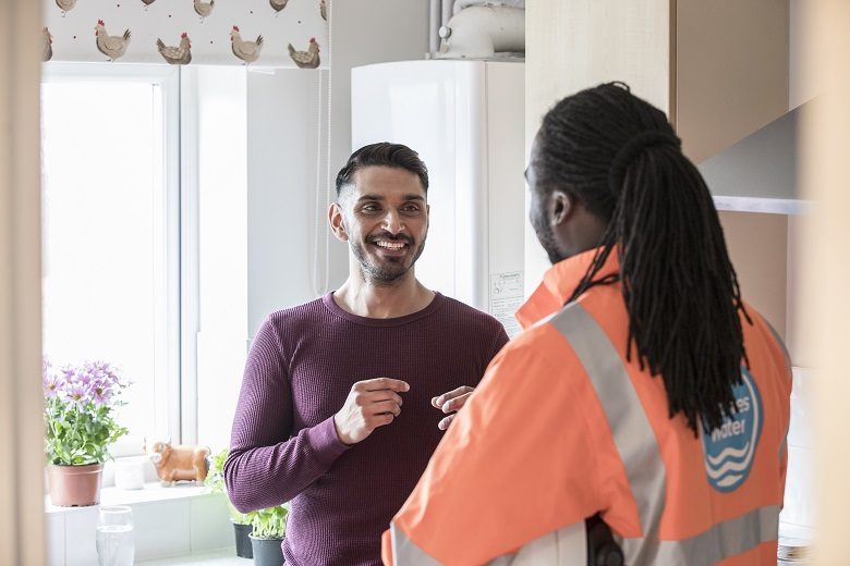 A Thames Water employee visiting a customer at their home