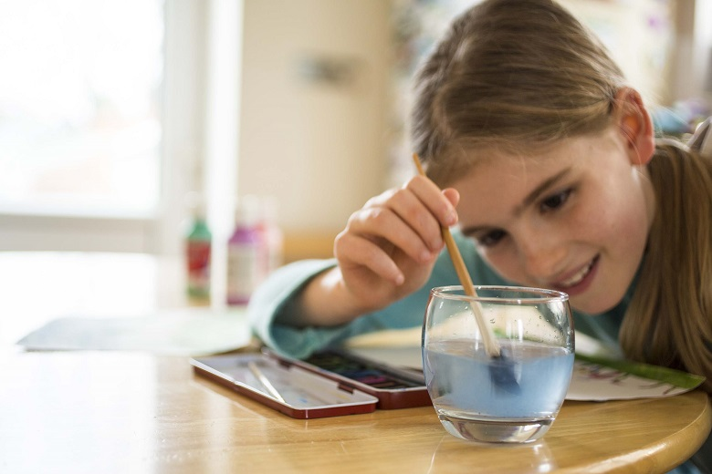 A child dipping a paintbrush in a glass of water