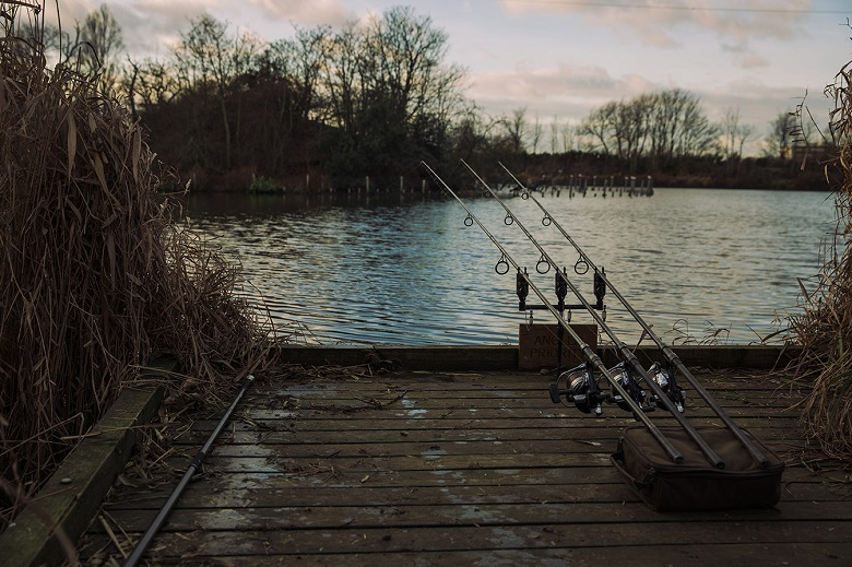 Three fishing rods propped up by a reservoir