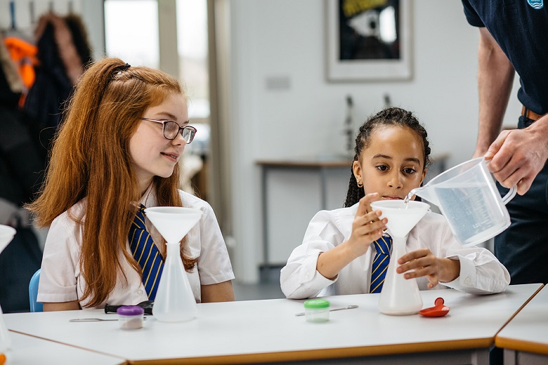 Children taking part in a water experiment with a Thames Water employee