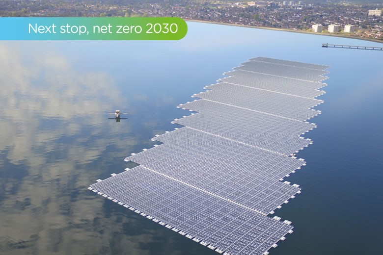 A picture of a series of solar power panels floating on the surface of water with clouds reflected in the surface.