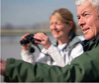 A man in a green jacket pointing beyond the shot with a woman in a white jacket with a pair of binoculars.