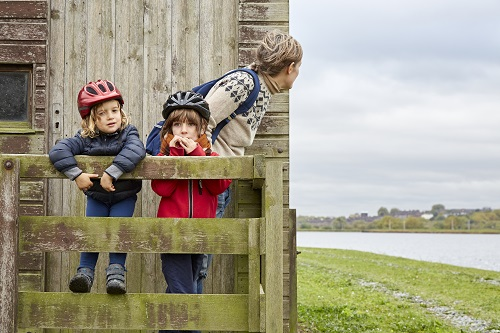 Two children looking at the camera wearing cycle helmets on a fence while an adult woman looks around the side of a wooden building.