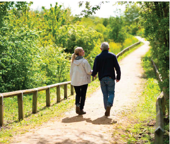 A man and woman hold hands walking along a footpath between woodland bushes and grassland in bright sunshine.
