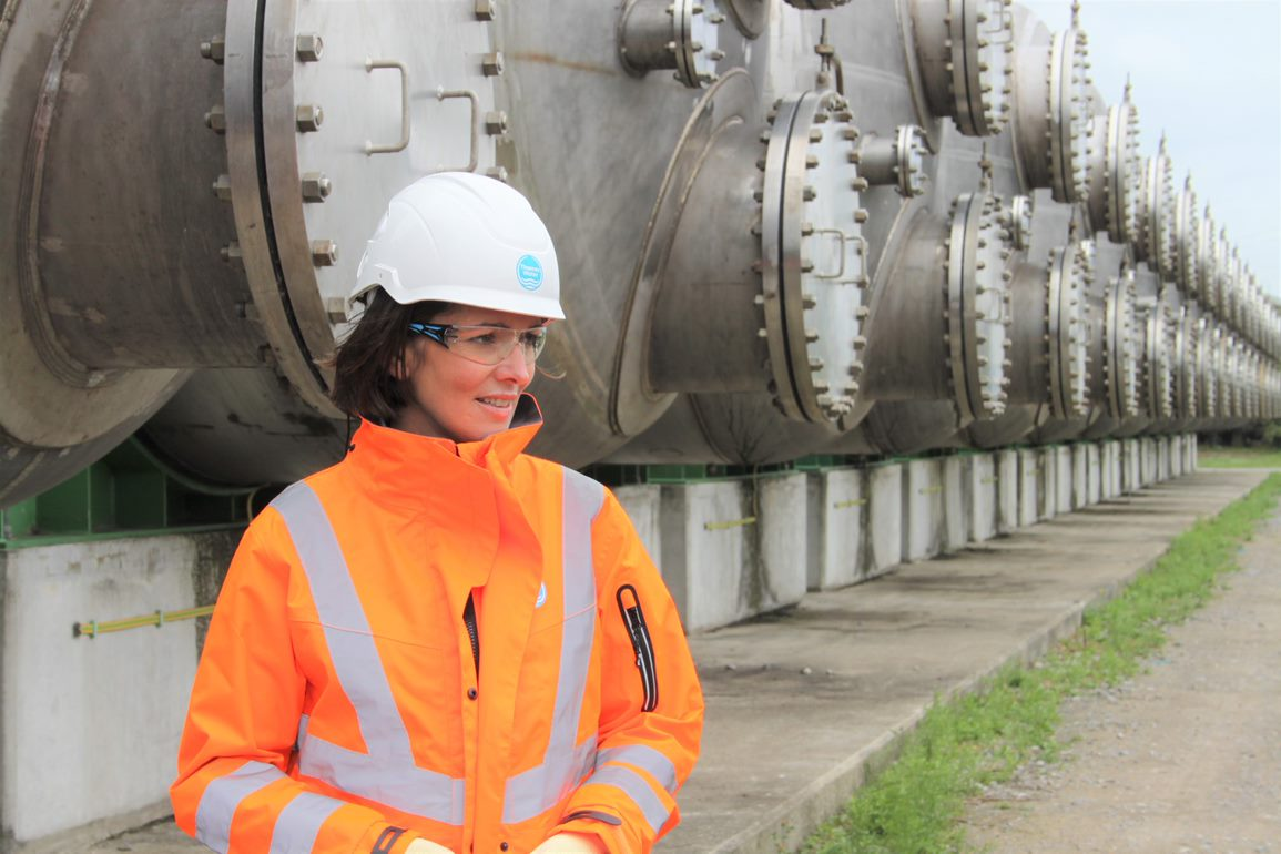 A picture of our CEO, Sarah Bentley, wearing an orange hi-vis jacket and white helmet with the Thames Water logo on.