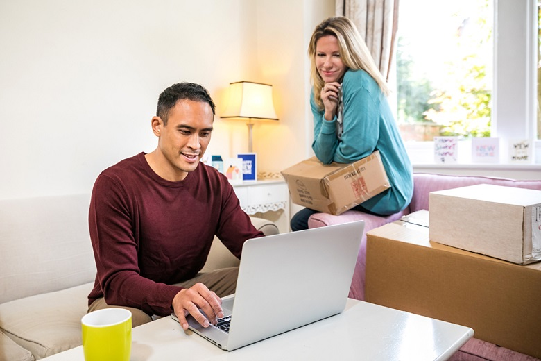A couple looking at a laptop screen amongst cardboard boxes