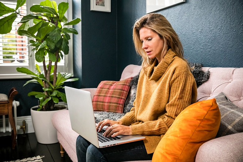 A customer sitting on a sofa while using a laptop