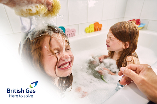 Two young children in the bath and one has soap bubbles on her hair.