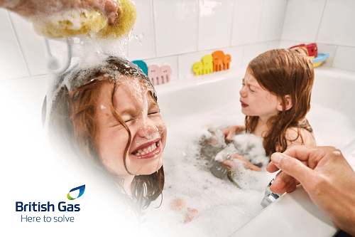 Two young girls in a bubble bath. One is having their hair washed with bubbles on their head.