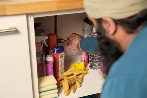 A man turning a stop valve in a kitchen cupboard