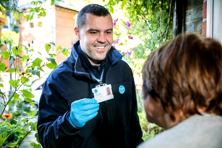 A Thames Water customer service rep showing their ID outside a customer's home
