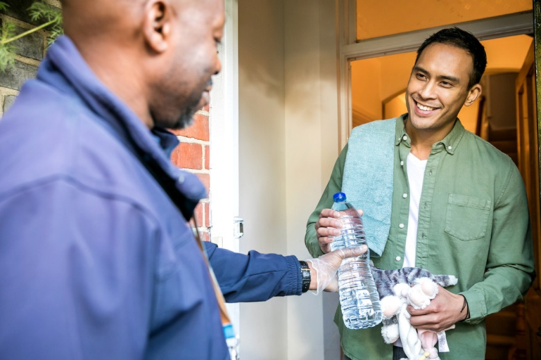 A Thames Water rep delivering bottled water to a priority services customer