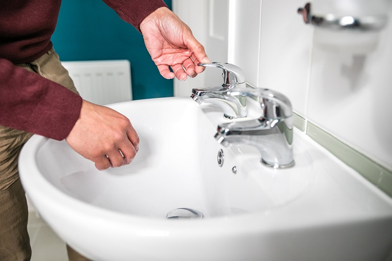 A close-up of hands turning on a bathroom sink tap