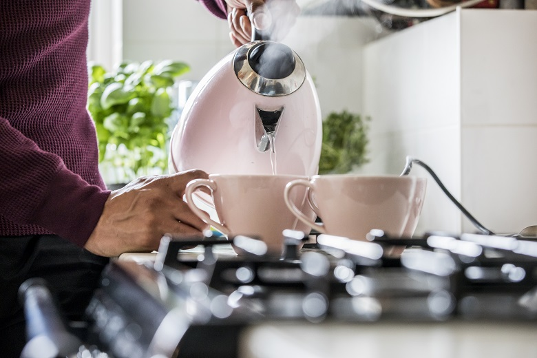 Person pouring water from a kettle into teacups