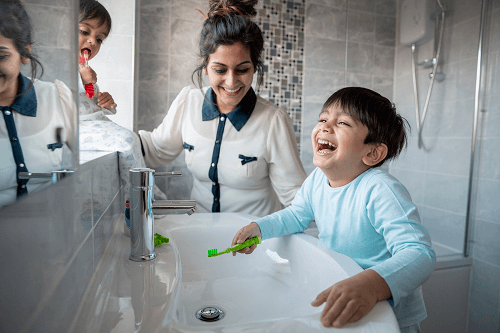 A mum helps her child to brush their teeth in the bathroom.